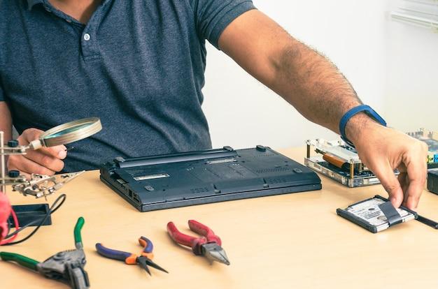 Computertechniker, der laptop auf dem schreibtisch repariert. schwarzer mann. werkzeuge.