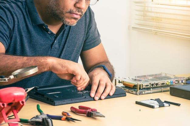 Computertechniker, der laptop auf schreibtisch repariert. schwarzer mann. werkzeuge.