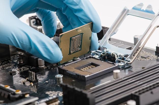 Computertechniker mit blauen handschuhen, der die cpu in das motherboard einbaut, nahaufnahme