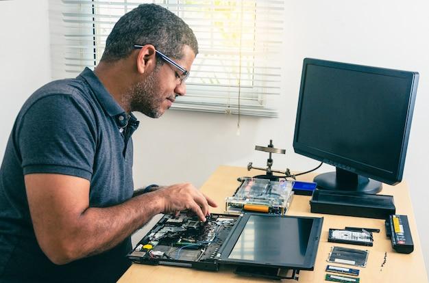 Computertechniker mit brille, laptop auf schreibtisch reparieren, mit werkzeugen herum. schwarzer mann. werkzeuge.
