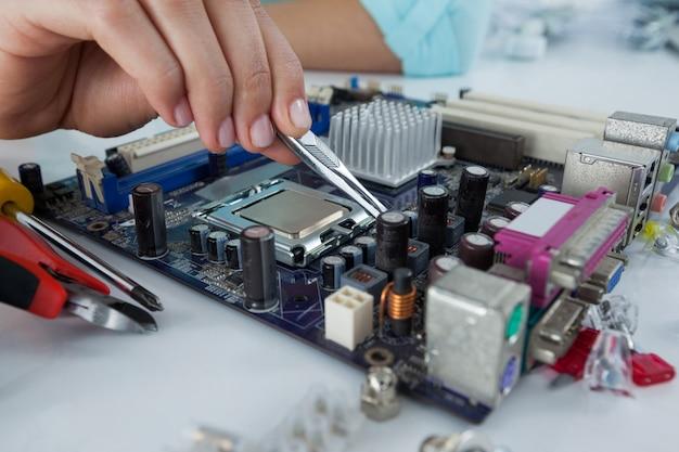 Computertechnikerin, die computer-motherboard repariert