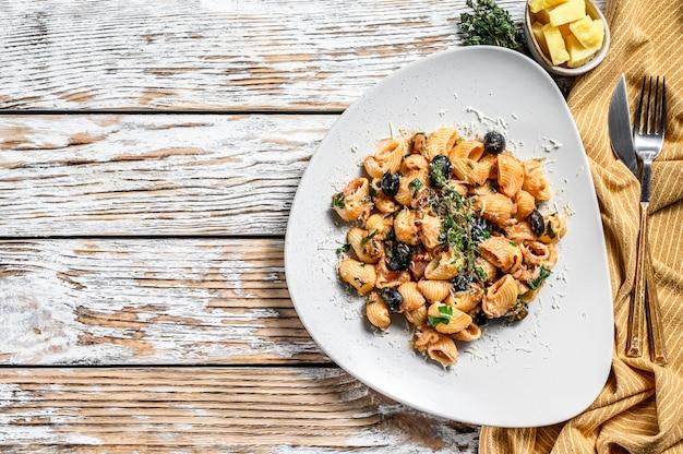 Conchiglie rigate italienische pasta mit tomaten, oliven, kapern, sardellen