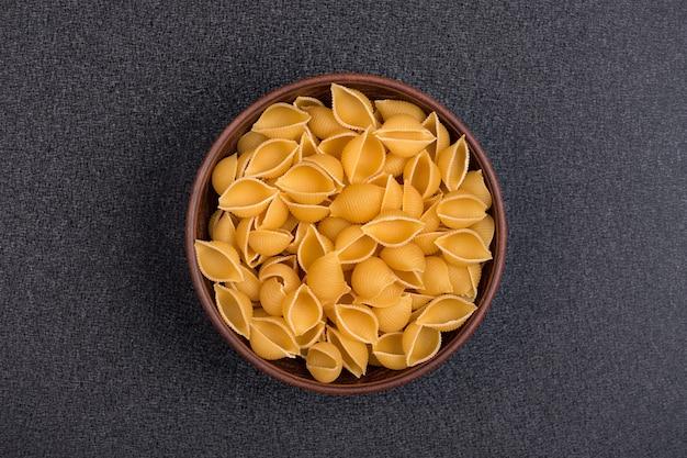 Conchilioni in der schüssel auf grauem hintergrund. ungekochte nudeln. pasta hintergrund