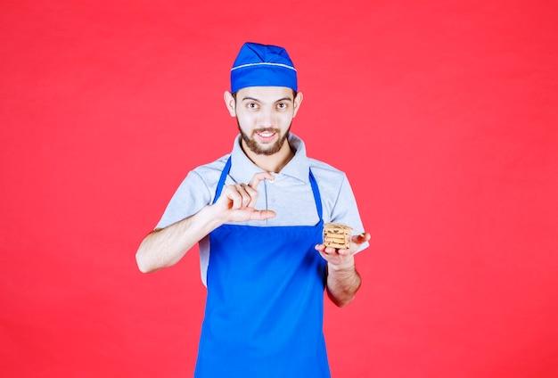 Conditer in blauer schürze hält einen vorrat an keksen und zeigt die menge an.