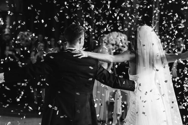 Confettie fällt über braut und bräutigam, während sie tanzen