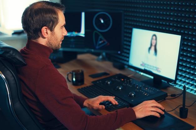 Confident man video editor arbeitet mit filmmaterial in creative office studio.