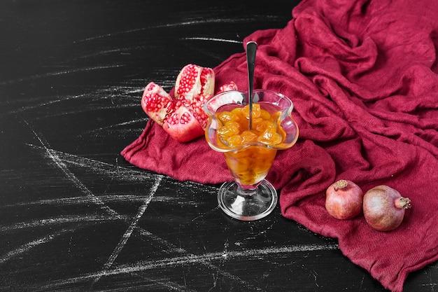 Confiture auf rotem handtuch mit granatapfel