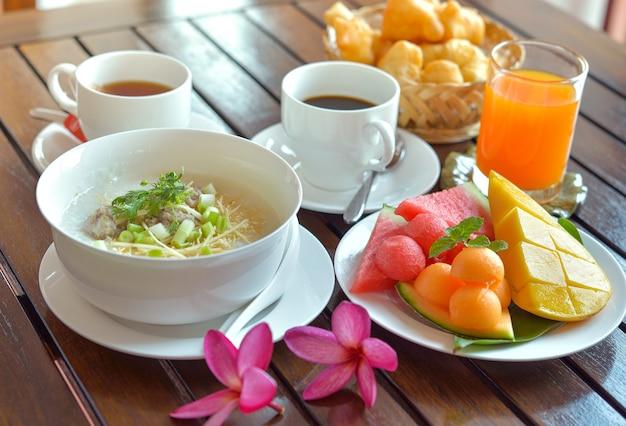Congee mit gehacktem schweinefleisch serviert ingwer koriander und ei, asiatisches essen frühstück