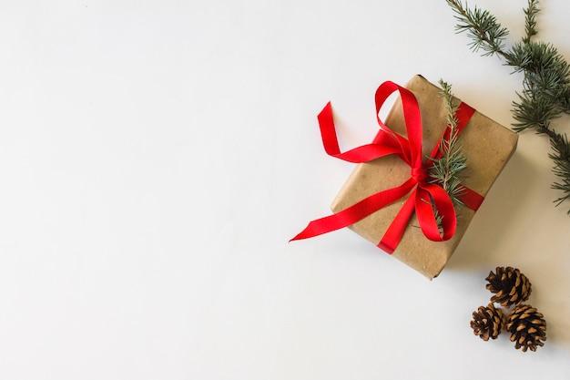 Conifer kegel und zweige in der nähe von geschenk
