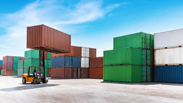 Container, der ladung mit gabelstapler stapelt, der im schifffahrtshafen arbeitet.
