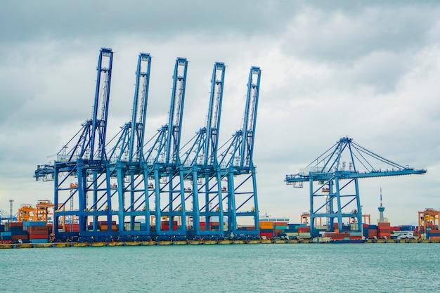 Containerfrachtschiff mit funktionierender kranladebrücke in der werft