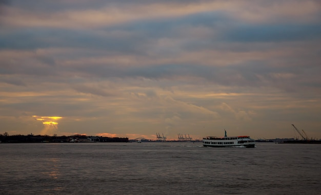 Containerkräne im hafen von new york bei sonnenuntergang und freiheitsstatue