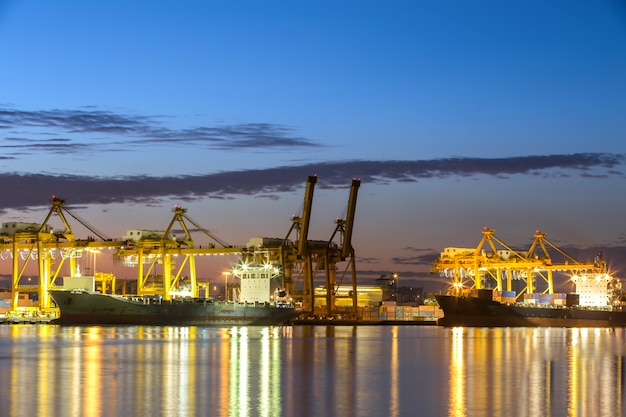 Containerschiff im hafen von hamburg, nachtaufnahme. bewölkter himmel.