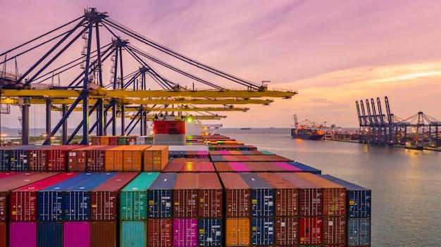 Containerschiffladen und -entladen in tiefseehafen bei sonnenuntergang, vogelperspektive des logistischen imports und des exports des geschäfts
