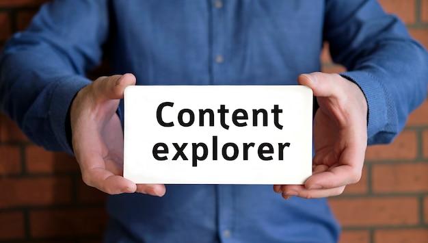 Content explorer - seo-konzept in den händen eines jungen mannes in einem blauen hemd