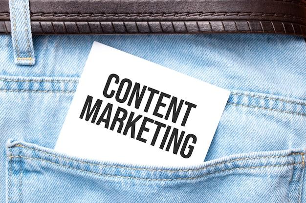 Content-marketing-wörter auf einem weißen papier ragten aus der jeanstasche. unternehmenskonzept.