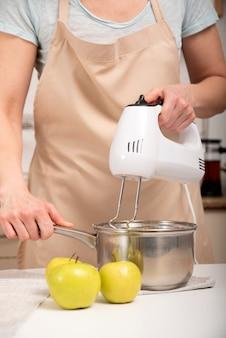 Cook bereitet einen apfelkuchen zu. mixer mischt die zutaten in einem topf. vertikaler rahmen.