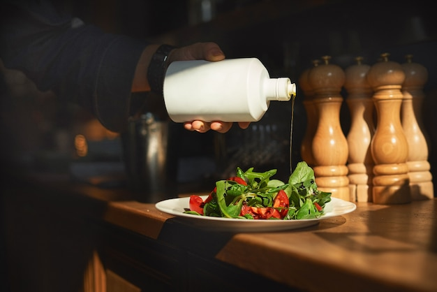 Cook gießt olivenöl auf einen frischen salat aus tomaten und grünem salat.