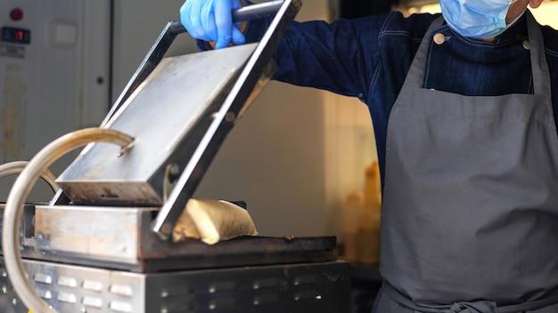Cook legt einen wrap zum backen in einen imbisswagen