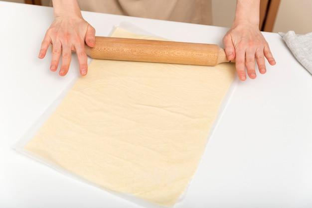 Cook rollt den teig dünn mit nudelholz aus