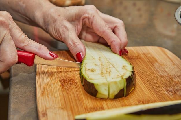 Cook schneidet die auberginen nach rezept auf einem holzbrett in der küche.