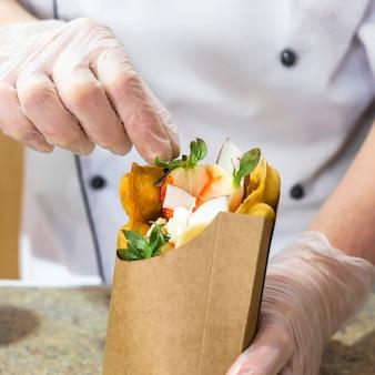 Cook verziert hongkong-waffeln mit erdbeeren und kokosnuss