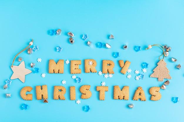 Cookies buchstaben frohe weihnachten auf blauer oberfläche.