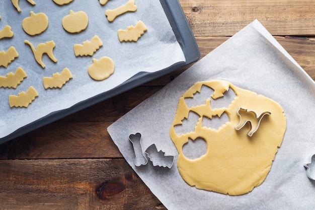Cookies in verschiedenen formen für halloween auf einem backblech. kekse vor dem backen schneiden. platz kopieren.