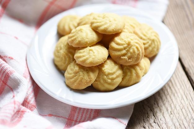 Cookies vanille auf weißem teller und holzuntergrund, mini-kekse kekse