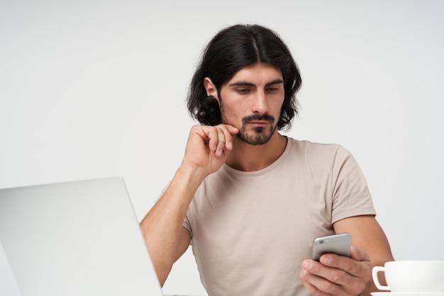 Cool aussehender männlicher, gutaussehender mann mit schwarzen haaren und bart. bürokonzept. kinn berühren und nachdenklich auf das smartphone schauen. sitzen am arbeitsplatz, isoliert nah oben über weißer wand