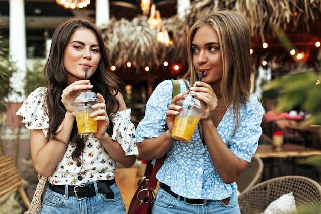 Cool gebräunte brünette und blonde frauen in jeanshosen und floralen stylischen blusen gehen gut gelaunt nach draußen und trinken limonade