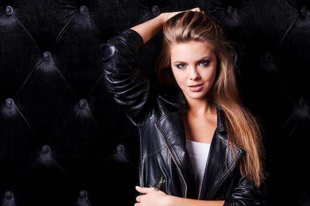 Cool und sexy. schöne junge frau mit make-up und frisur posiert vor schwarzem hintergrund