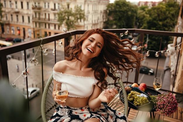 Coole dame lacht und posiert mit champagner auf der terrasse
