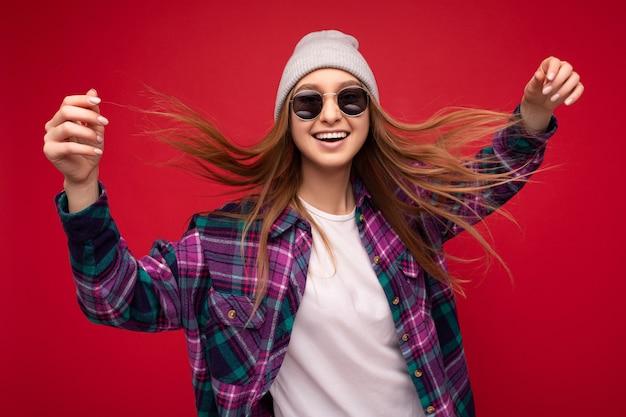 Coole fotoaufnahme einer schönen, glücklich lächelnden jungen blonden frau, die über rotem hintergrund isoliert ist