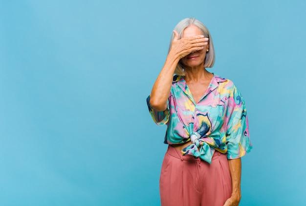 Coole frau mittleren alters, die augen mit einer hand bedeckt, die sich ängstlich oder ängstlich fühlt, sich wundert oder blind auf eine überraschung wartet
