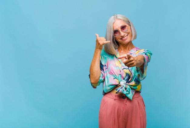 Coole frau mittleren alters, die fröhlich lächelt und auf die kamera zeigt, während sie einen anruf tätigen, den sie später gestikulieren und am telefon sprechen