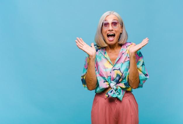 Coole frau mittleren alters, die glücklich und aufgeregt aussieht, schockiert von einer unerwarteten überraschung mit beiden händen offen neben gesicht