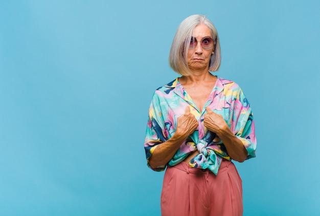 Coole frau mittleren alters, die mit einem verwirrten und fragenden blick auf sich selbst zeigt, schockiert und überrascht, ausgewählt zu werden