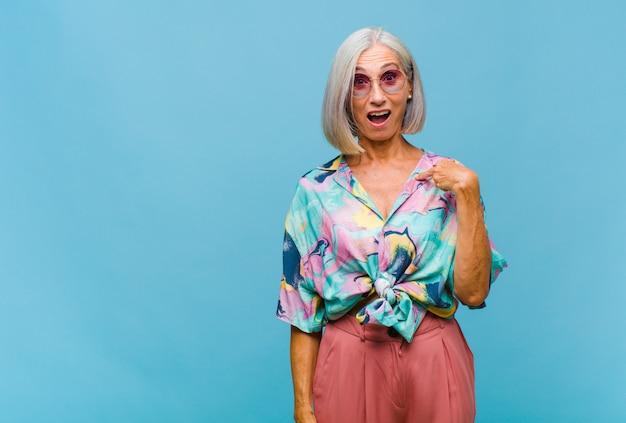 Coole frau mittleren alters, die schockiert und überrascht mit offenem mund aussieht und auf sich selbst zeigt