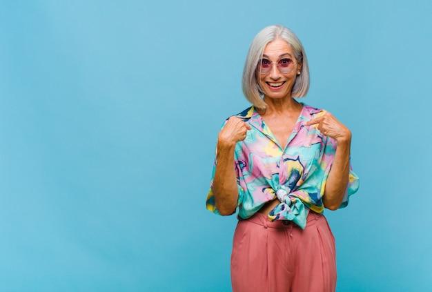 Coole frau mittleren alters, die sich glücklich, überrascht und stolz fühlt und mit einem aufgeregten, erstaunten blick auf sich selbst zeigt
