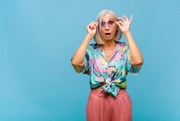 Coole frau mittleren alters, die sich schockiert, erstaunt und überrascht fühlt und eine brille mit einem erstaunten, ungläubigen blick hält