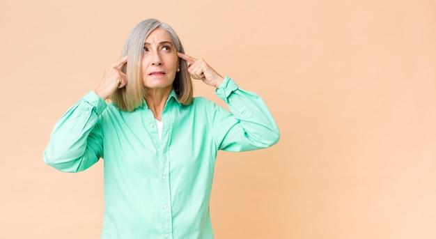Coole frau mittleren alters, die sich verwirrt oder zweifelnd fühlt, sich auf eine idee konzentriert, hart nachdenkt und versucht, platz auf der seite zu kopieren