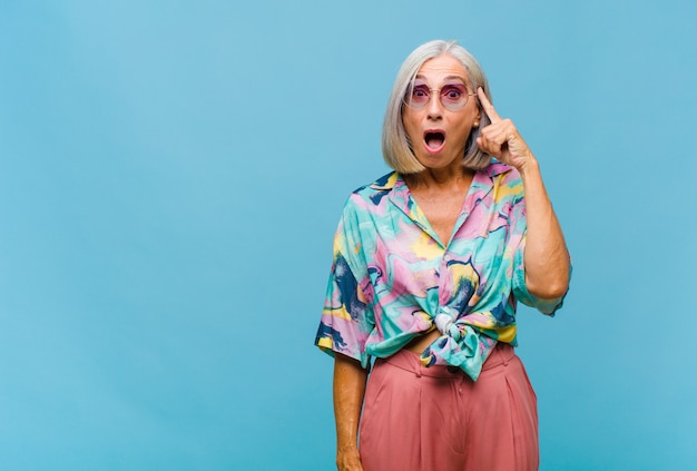 Coole frau mittleren alters, überrascht, mit offenem mund, schockiert, einen neuen gedanken realisierend