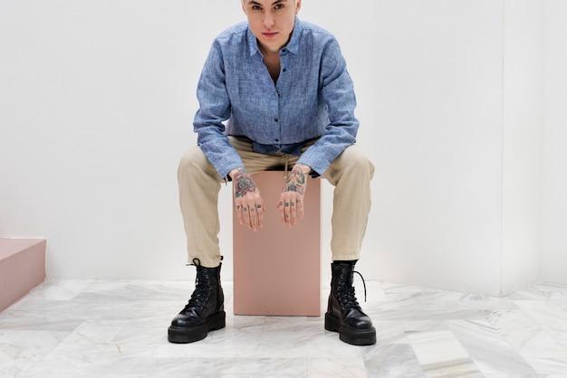 Coole frau sitzt auf einer rosa kiste