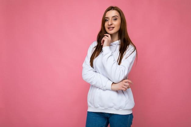 Coole junge kaukasische schöne brünette frau mit aufrichtigen emotionen auf hintergrundwand mit isoliert