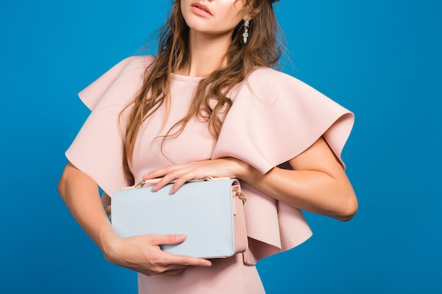Coole junge stilvolle sexy frau im rosa luxuskleid, sommermodetrend, schicker stil, blauer studiohintergrund, hält trendige handtasche