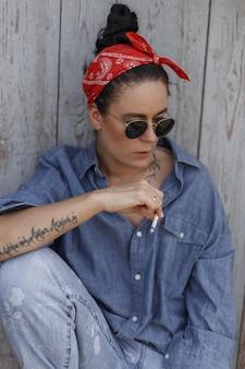 Coole modische schöne amerikanische hipster-modellfrau mit sonnenbrille in blauen vintage stilvollen jeanskleidern und jeans, die nahe einer holzwand sitzen