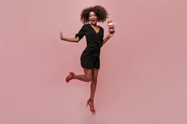 Coole mulattin mit flauschiger brünette frisur in schwarzem kleid und roten modernen absätzen springt, lächelt und hält geschenkbox