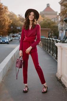 Coole schöne stilvolle frau im lila anzug, die in stadtstraße, frühlingssommer-herbstsaison-modetrend trägt hut trägt und geldbörse hält