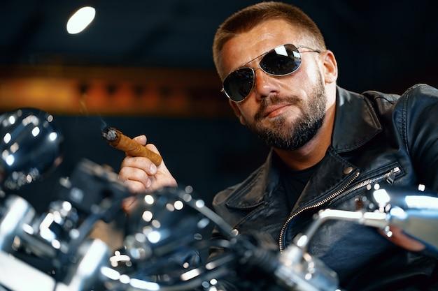 Cooler bärtiger mannbiker in der sonnenbrille, die auf seinem motorrad sitzt und zigarre raucht